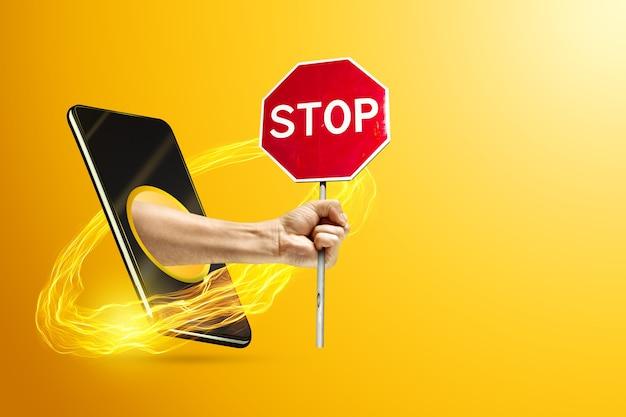 Рука держит знак остановки через смартфон