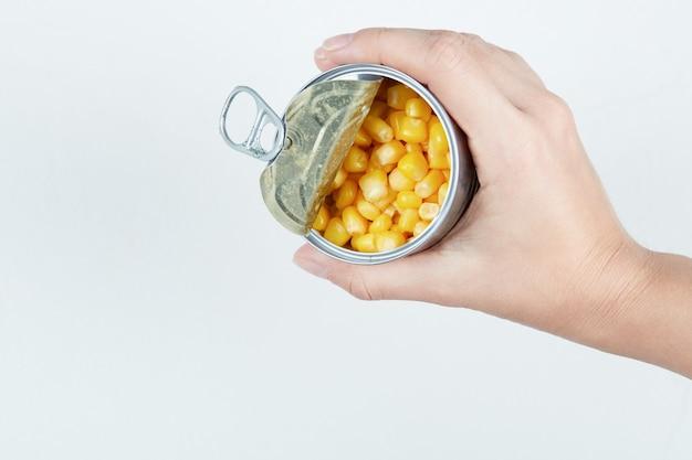 ゆでたスイートコーンの缶を持っている手。