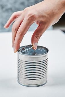 白いテーブルの上にゆでたグリーンピースと缶を持っている手。