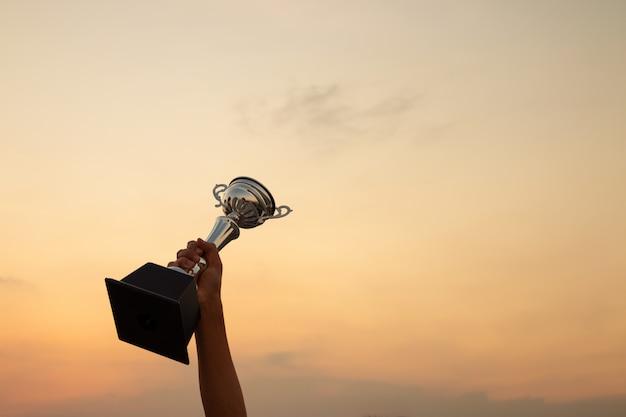 Рука держит трофей на закате