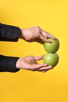 Рука держит два яблока на желтом фоне