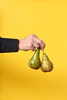 Рука держит две груши на желтом фоне
