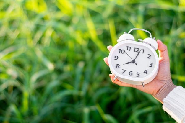 Рука белый будильник в природе. - концепция идей мышления и контроля времени.