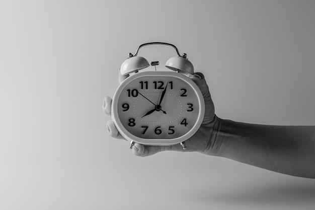 白い目覚まし時計を持っている手。 -思考とタイミングのアイデアのコンセプトを制御します。