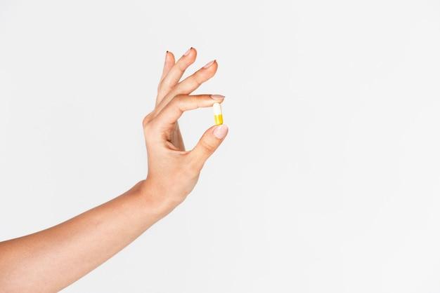 흰색과 노란색 알약을 들고 손