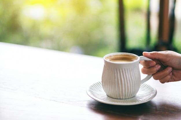 Рука держит белую чашку горячего кофе на деревянном столе