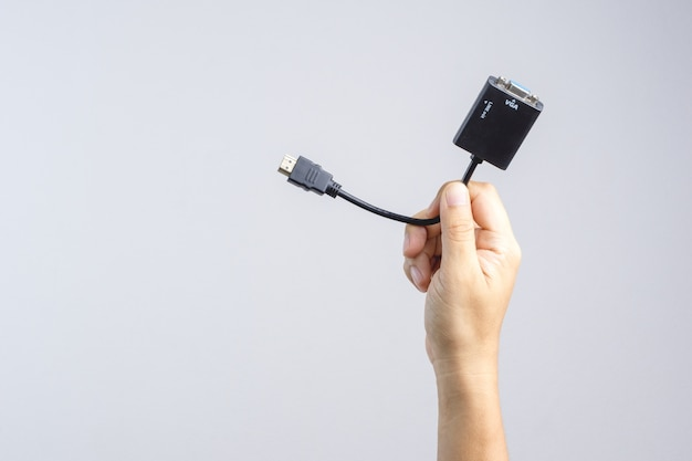 Hand holding adaptor hdmi to vga cable connector