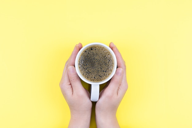 アメリカーノコーヒーと白いカップを持っている手