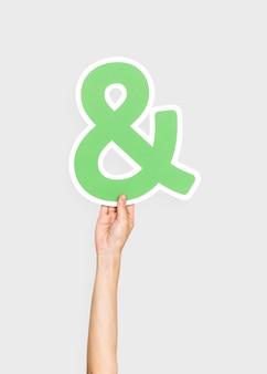 Hand holding ampersand symbol