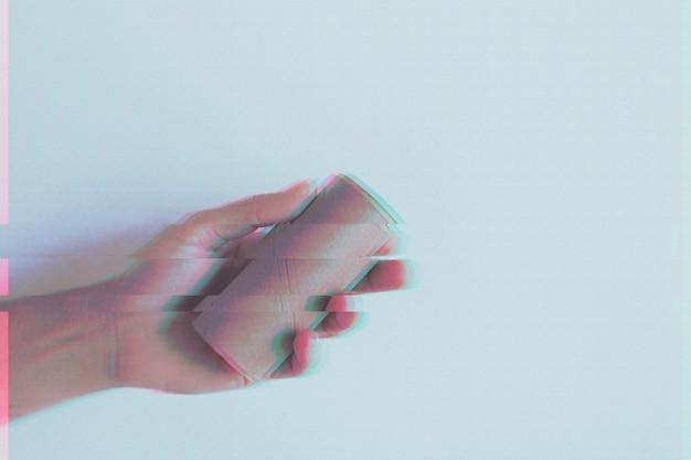 空のトイレットペーパーロールを持っている手