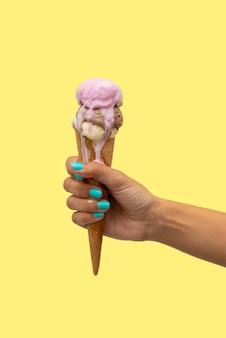 黄色でアイスクリームを持っている手