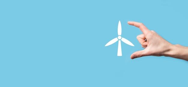 파란색 배경에 환경 에너지를 생산하는 풍차 아이콘을 손에 들고 있습니다.