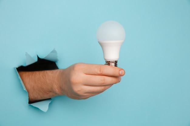 Рука держит лампочку накаливания из разорванной дыры в синей бумаге