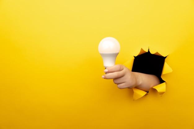 黄色い紙の破れた穴から白熱電球を持っている手。