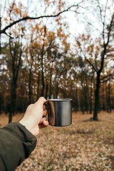 温かい飲み物と鉄のコップを持っている手