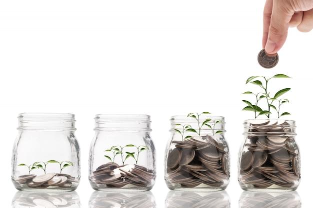 Рука держа и положить монету для сохранения стеклянной банке с растений светящихся и роста на монетах.