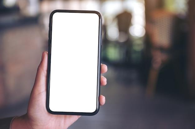 Рука держит и показывает черный мобильный телефон с пустым белым экраном в современном кафе