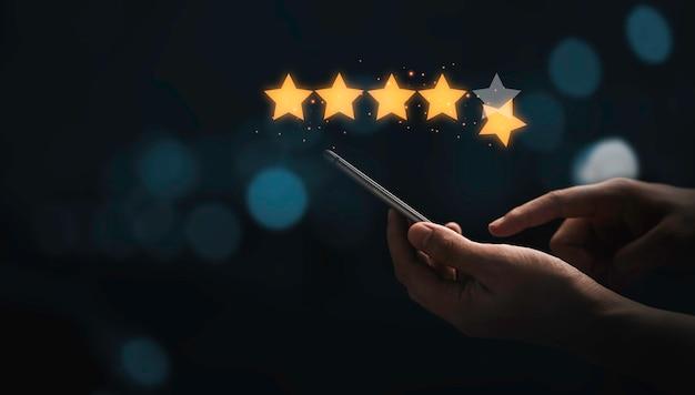 제품 및 서비스 개념을 사용한 후 최고의 고객 고객 평가 점수를 위해 빛나는 빛이 있는 가상의 황금 별 5개가 있는 스마트폰을 손에 들고 사용합니다.
