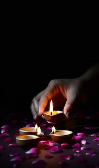 Hand holding and arranging lantern (diya) during diwali festival of lights
