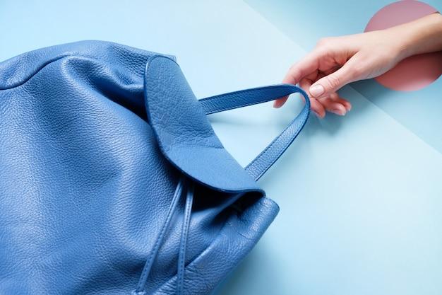 Рука рюкзак на синем столе. трендовая дыра