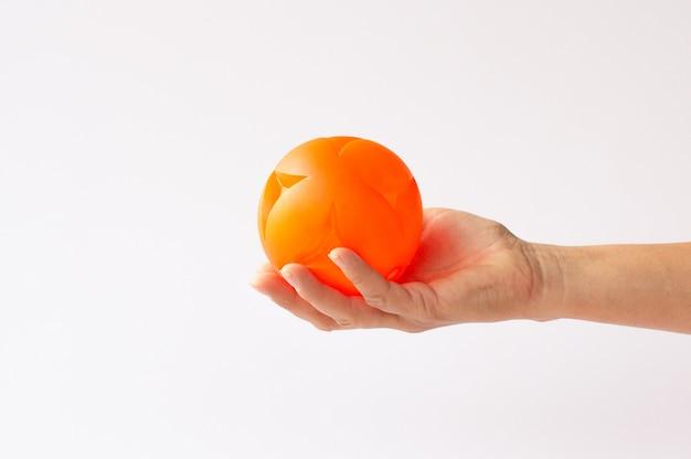 白い背景で隔離のボールのおもちゃを持っている手