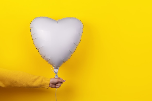 Hand holding ballon in shape of heart over yellow background, holiday concept with love