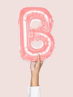 Hand holding balloon letter b