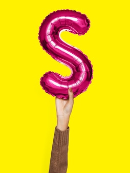 Hand holding balloon letter s