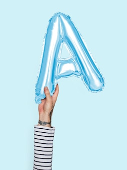 Hand holding balloon letter a
