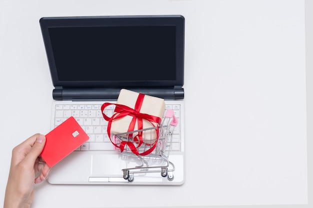 Hand holding bank credit card, laptop with blank black screen and gift in shopping trolley, copy space. online shopping, internet commerce. online e-commerce shopping interface concept.
