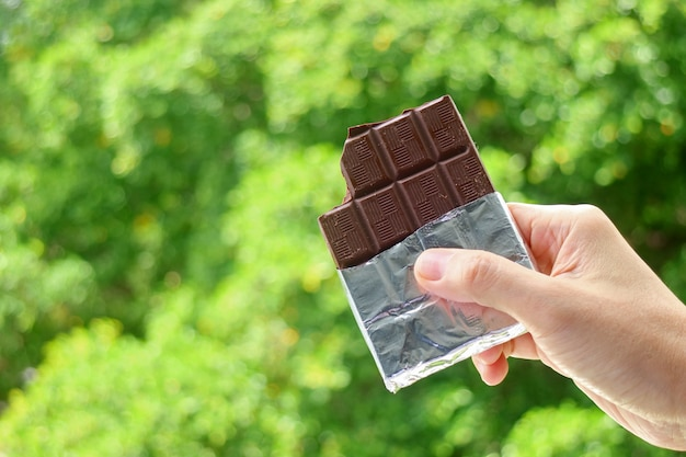 Hand holding a bar of dark chocolate in foil pack with blurry green foliage in the backdrop