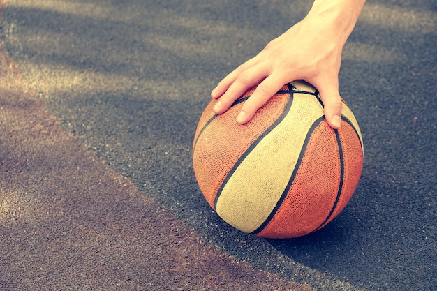 Hand holding a basket ball. toned