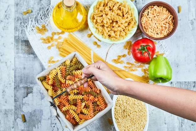 Hand holding a basket of raw fusilli pasta with assorted pastas and vegetable on the marble table.