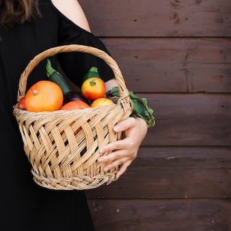 Hand holding basket with vegetables