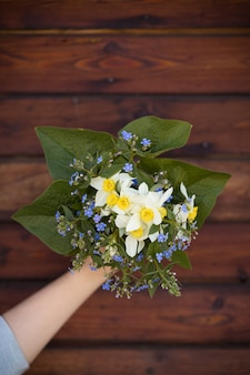 Hand holding a beautiful bunch of spring and summer flowers on old wooden background garden bouquet
