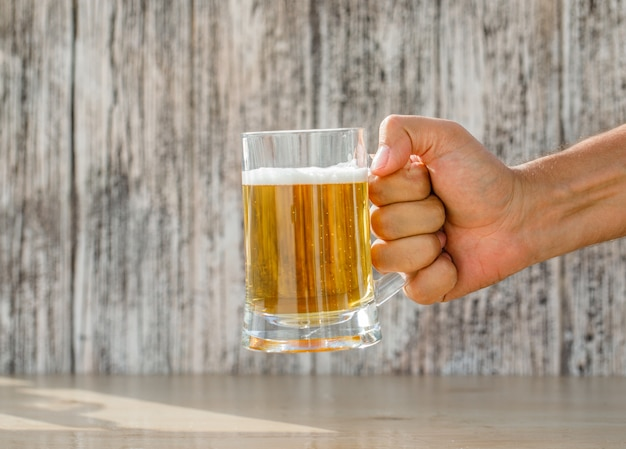 Hand holding beer in a glass mug on grungy and light table, side view.