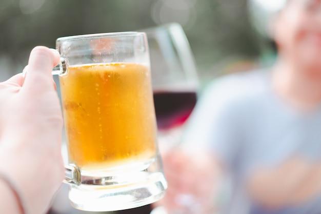 Hand holding beer mug smash with wine glass at restaurant