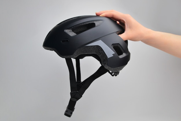 Hand holding bicycle safety helmet for mountain bike