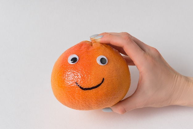 Hand holding big orange smiley on white background. grapefruit with googly eyes and smile