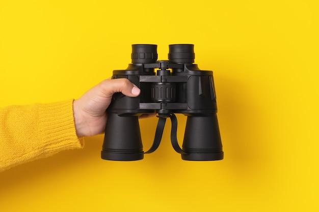 노란색 배경 위에 쌍안경을 들고 손