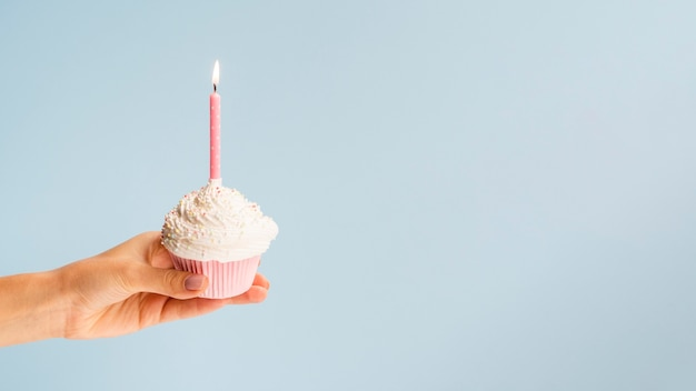 Hand holding birthday muffin on blue background