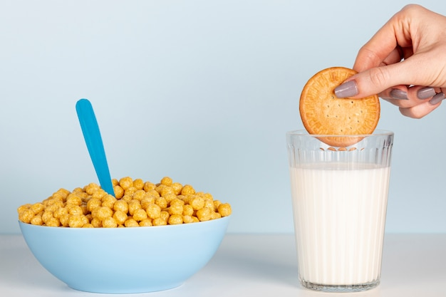 Hand holding a biscuit above milk and bowl of cereals