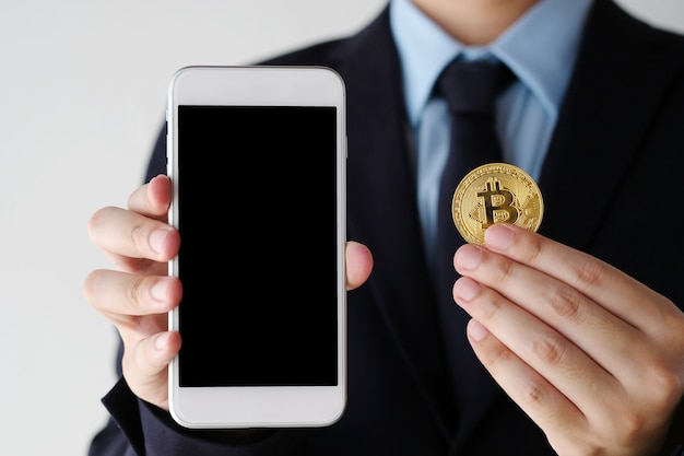 空白の画面の背景とビットコインとスマートフォンを保持する手