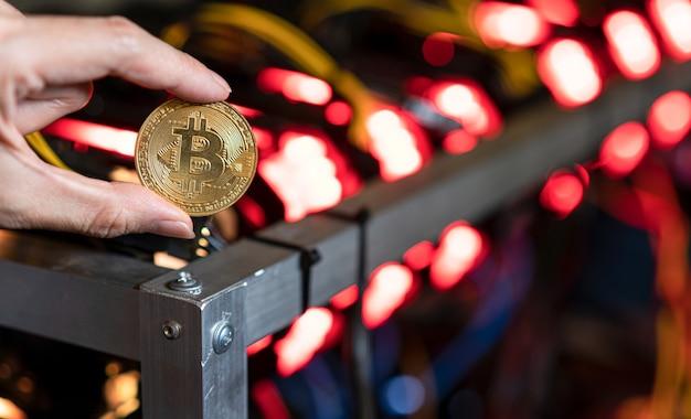 Hand holding bitcoin on bitcoin mining farm background