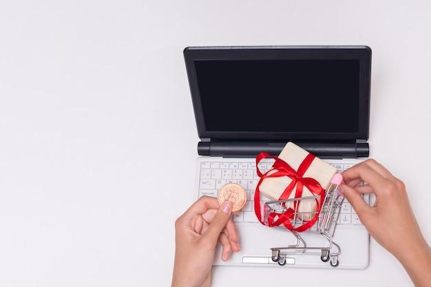 비트코인 동전을 들고 있는 손, 빈 검은색 화면이 있는 노트북, 쇼핑 카트에 선물, 복사 공간. 온라인 쇼핑, 인터넷 상거래. 온라인 전자 상거래 쇼핑 인터페이스 개념입니다.