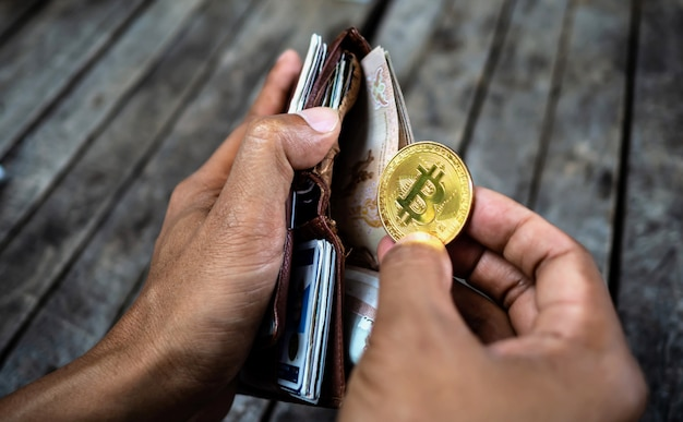 Hand holding bitcoin coin with wallet