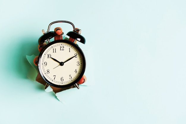Hand holding black alarm clock through hole in blue paper background. wake up alert concept.