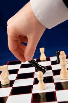 Hand holding black chessman