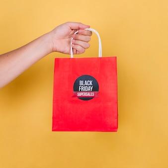 Hand holding black friday bag