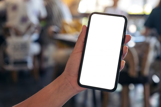 A hand holding black mobile phone with blank desktop screen with blur background in cafe